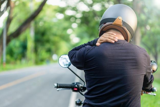 Motorrijder met pijn of moe concept: man rijder raakt zijn nek of schouder aan en voelt zich moe na een lange rit motorfiets. buiten fotograferen op de weg met kopie ruimte