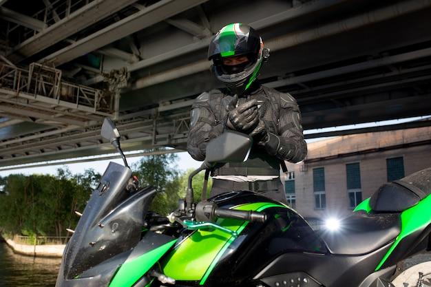Motorrijder stopt onder de brug over de weg, wachtend tot de regen stopt