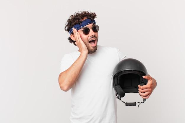 Motorrijder voelt zich gelukkig, opgewonden en verrast, kijkend naar de zijkant met beide handen op het gezicht