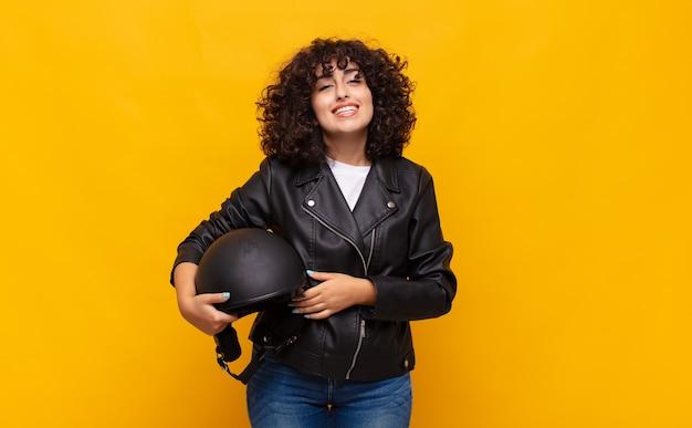 Motorrijder vrouw die er blij en aangenaam verrast uitziet, opgewonden met een gefascineerde en geschokte uitdrukking