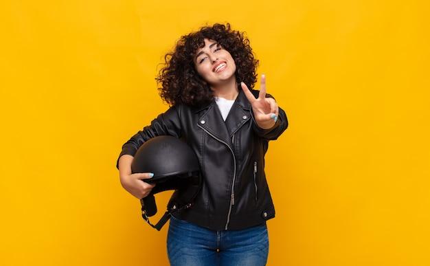 Motorrijder vrouw glimlacht en kijkt gelukkig, zorgeloos en positief, gebaren overwinning of vrede met één hand