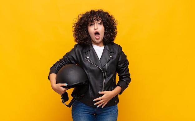 Motorrijder vrouw kijkt erg geschokt of verrast, starend met open mond en zegt wow