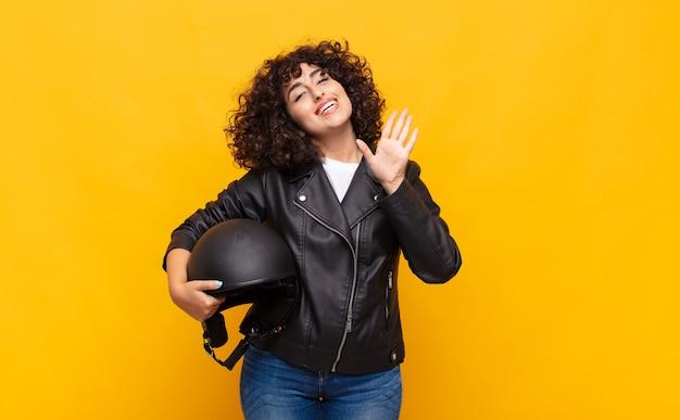 Motorrijder vrouw lacht vrolijk en opgewekt, zwaait met de hand, verwelkomt en begroet je, of neemt afscheid