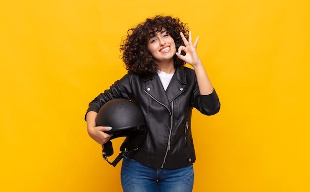 Motorrijder vrouw voelt zich gelukkig, ontspannen en tevreden, toont goedkeuring met goed gebaar, glimlachend
