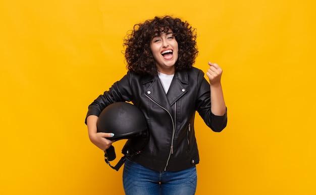 Motorrijder vrouw voelt zich geschokt, opgewonden en gelukkig, lacht en viert succes, zegt wow!