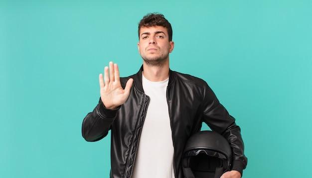 Motorrijder ziet er serieus, streng, ontevreden en boos uit en laat een open handpalm zien die een stopgebaar maakt