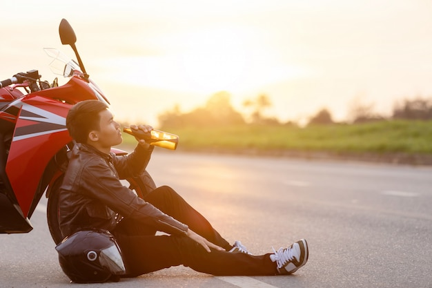 Motorrijder zittend op de weg naast zijn motorfiets, het drinken van een alcohol of bier