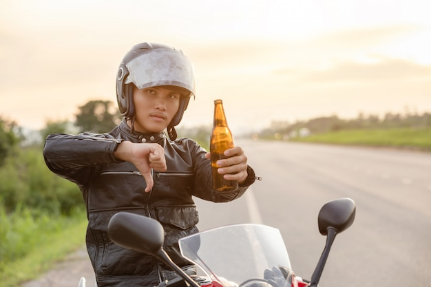 Motorrijder zittend op zijn motorfiets, toon hand met symbool geen alcohol of bier drinken