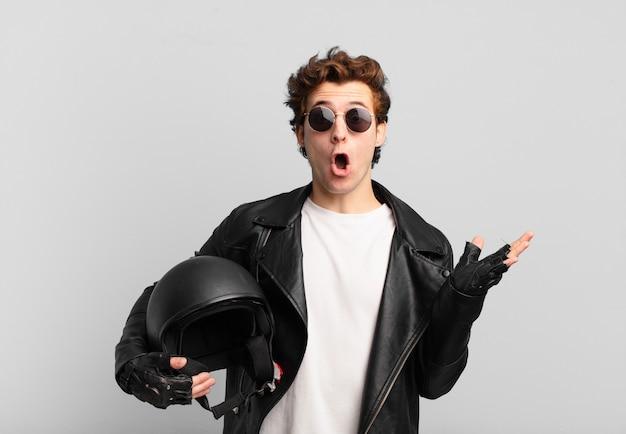 Motorrijderjongen die verrast en geschokt kijkt, met open mond terwijl hij een object vasthoudt met een open hand aan de zijkant