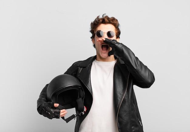 Motorrijderjongen die zich gelukkig, opgewonden en positief voelt, een grote schreeuw geeft met de handen naast de mond, roept