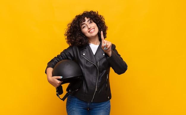 Motorrijdervrouw die en vriendelijk glimlacht kijkt, nummer één toont of eerst met vooruit hand, aftellend