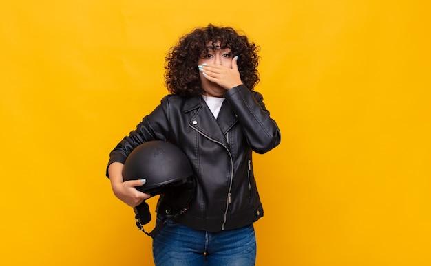 Motorrijdervrouw die mond bedekt met handen met een geschokte, verbaasde uitdrukking, een geheim bewaren of oeps zeggen
