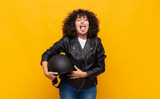 Motorrijdervrouw met vrolijke, zorgeloze, rebelse houding, grappen maken en tong uitsteken, plezier maken