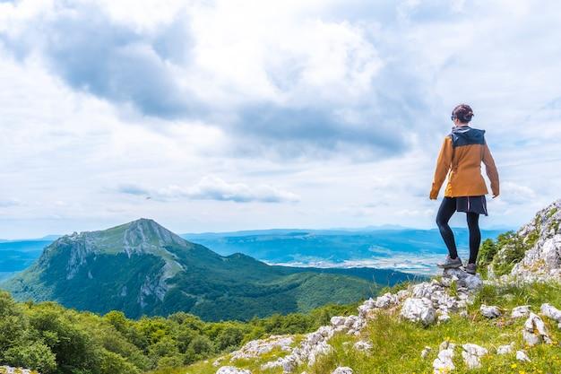 Mount aizkorri 1523 meter, de hoogste in guipuzcoa. baskenland. een jonge vrouw met een gele jas omhoog op de top. klim door san adrian en keer terug door de oltza-velden