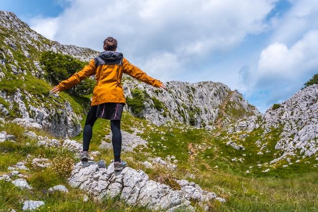 Mount aizkorri 1523 meter, de hoogste in guipuzcoa. baskenland. een jonge vrouw met een gele jas op de top. klim door san adrian en keer terug door de oltza-velden