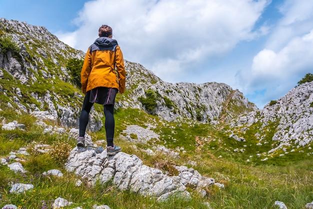 Mount aizkorri 1523 meter, de hoogste in guipuzcoa. baskenland. een jonge wandelaar met een gele jas op de top. klim door san adrian en keer terug door de oltza-velden