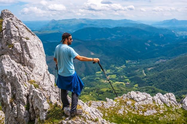 Mount aizkorri 1523 meter, de hoogste in guipuzcoa. baskenland. klim door san adrian en keer terug door de oltza-velden. een jonge man die de trekking voltooit en van bovenaf naar het uitzicht kijkt