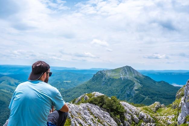 Mount aizkorri 1523 meter, de hoogste in guipuzcoa. baskenland. klim door san adrian en keer terug door de oltza-velden. een jonge man in een blauw shirt kijken naar de uitzichten van bovenaf
