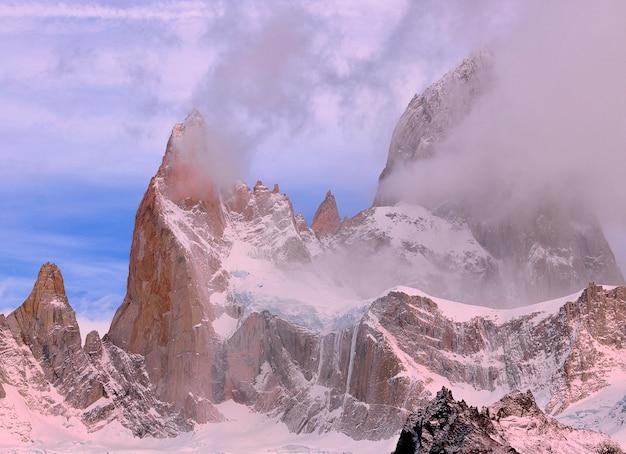 Mount fitzroy bij zonsondergang. roze wolken en blauwe lucht. nationaal park los glaciares. el chalten. andes. argentinië. zuid-amerika