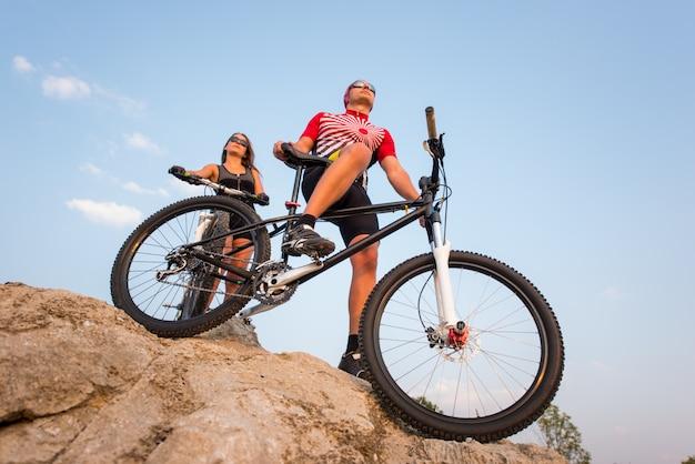 Mountainbike en rijder tegen blauwe hemel