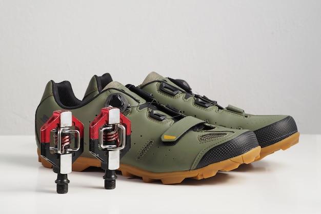 Mountainbike schoenen en rode pedalen.