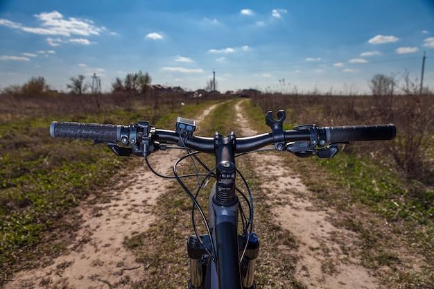 Mountainbiken bergafwaarts snel afdalend op de fiets. uitzicht vanuit de ogen van motorrijders.