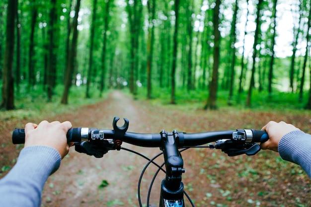 Mountainbiken bergafwaarts snel aflopend op de fiets. uitzicht vanuit de ogen van motorrijders.
