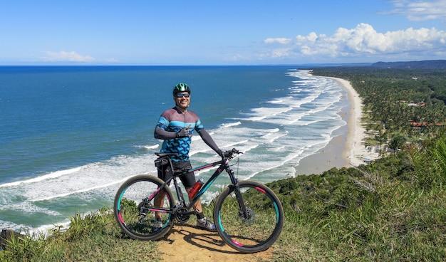 Mountainbiker fietsen in de bergen en op het strand fitness motivatie inspiratie in een prachtig inspirerend uitzicht