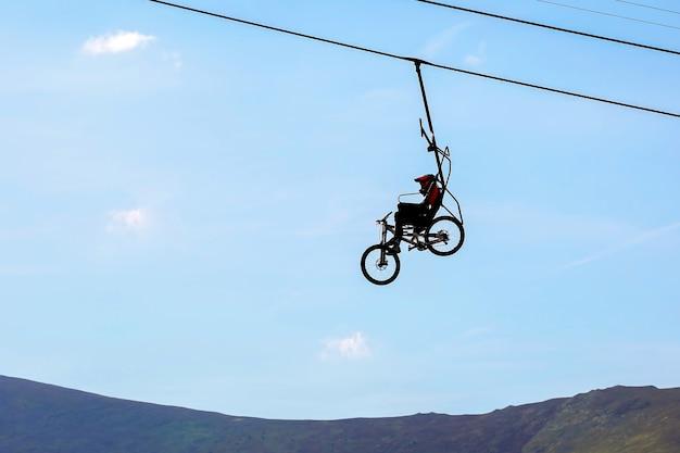 Mountainbiker klimt op de kabelbaan