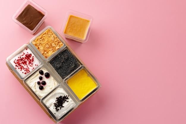 Mousse desserts in plastic dozen op roze achtergrond bovenaanzicht