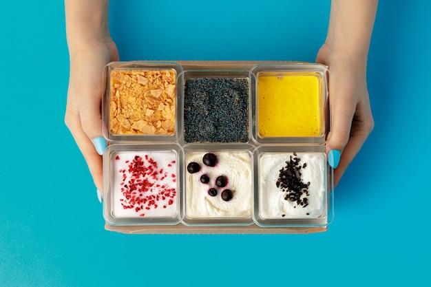 Mousse desserts in vierkante plastic dozen met verschillende toppings op roze tafel, bovenaanzicht
