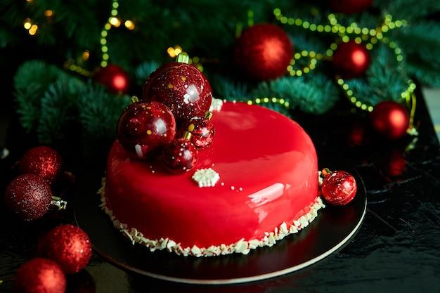 Mousse kerst gebak cake dessert bedekt met rode spiegelglazuur met nieuwjaarsversieringen op guirlande lampen bokeh donkere achtergrond, moderne europese cake kerstthema.