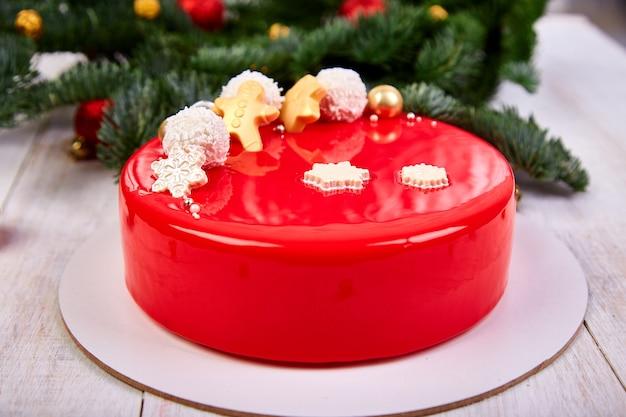 Mousse kerst gebak taart dessert bedekt met rode spiegel glazuur met nieuwjaarsversieringen op slinger lampen bokeh witte achtergrond, moderne europese cake kerstthema.