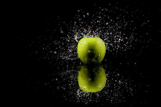 Mousserend water valt op sappige groene appel die op zwarte tafel staat