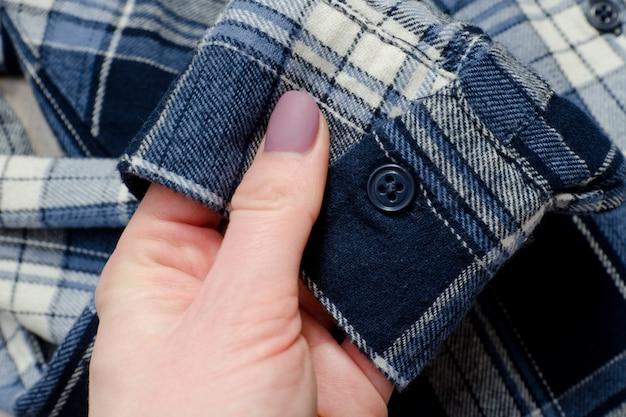 Mouw van blauw geruit hemd in vrouwelijke hand. detailopname.