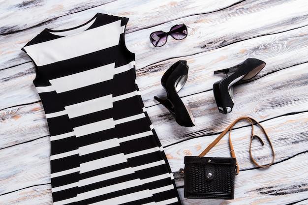 Mouwloze jurk en schoenen met hak, zonnebril en zwarte portemonnee trendy avondoutfit voor dames designer...