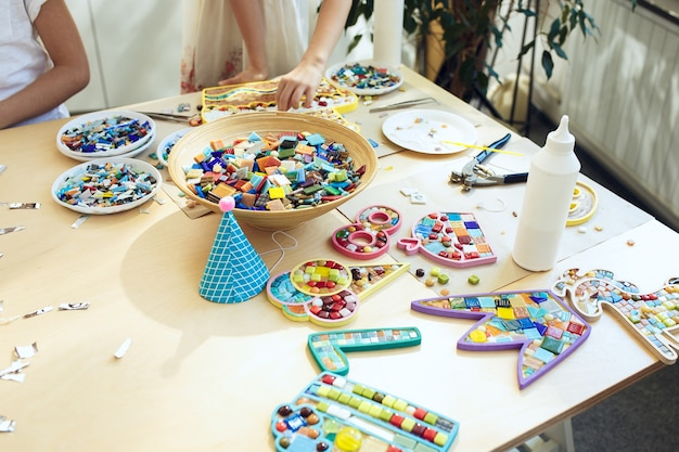 Mozaïek puzzelkunst voor kinderen, creatief spel voor kinderen. handen spelen mozaïek aan tafel. close-up van kleurrijke veelkleurige details.