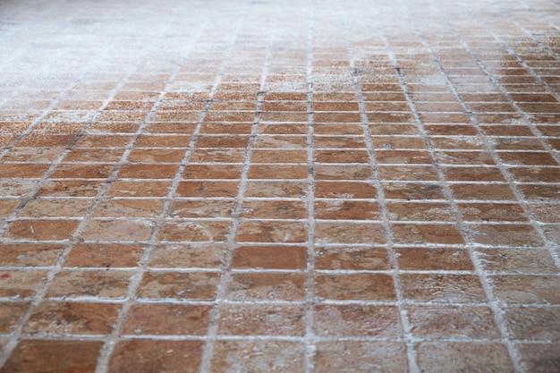 Mozaïek stenen vloer bedekt met sneeuw
