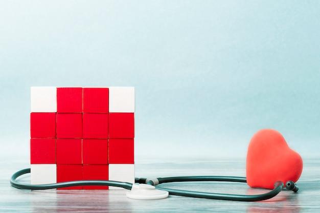 Mozaïek van kubussen in de vorm van een rood kruis verstrengeld met een statoscoop. aan de andere kant van het hart. het concept van geneeskunde, help.