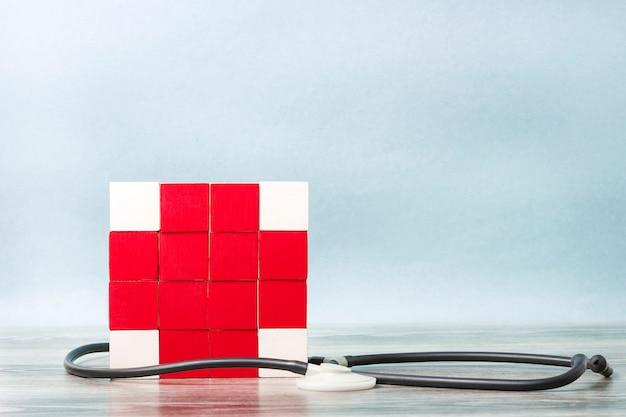 Mozaïek van kubussen in de vorm van een rood kruis verstrengeld met een statoscoop. concept geneeskunde, hulp.