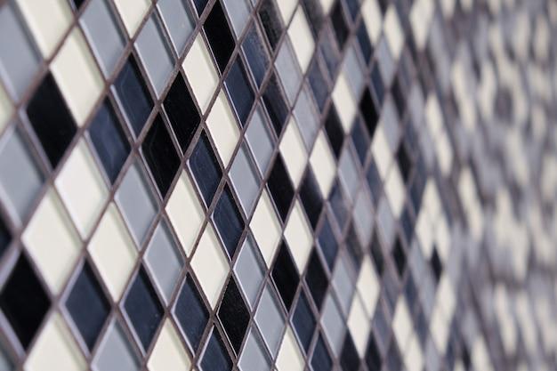 Mozaïekachtergrond van zwarte, witte en grijze keramische vierkante tegels.