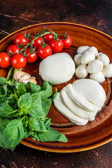 Mozzarella kaas, basilicum en tomaat kers klaar voor het koken caprese salade. donkere achtergrond. bovenaanzicht.