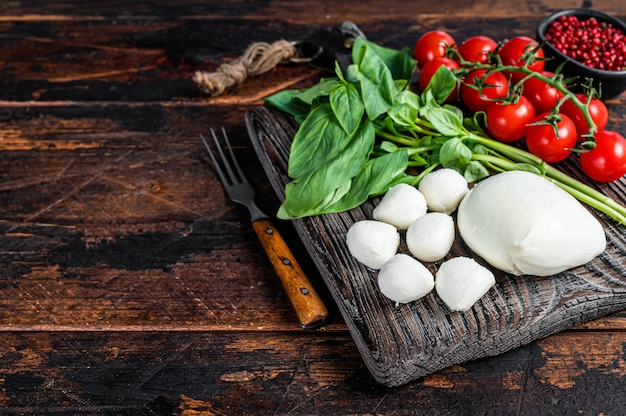 Mozzarella kaas, basilicum en tomaat kers op houten plank
