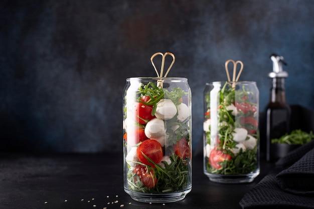 Mozzarella met kerstomaatjes en rucola in een glazen pot op een donkere achtergrond