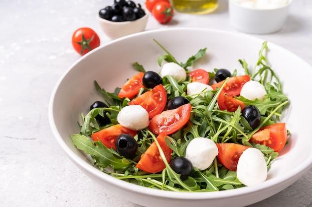 Mozzarella salade met tomaten, zwarte olijven, rucola en olijfolie. gerecht van de italiaanse griekse keuken