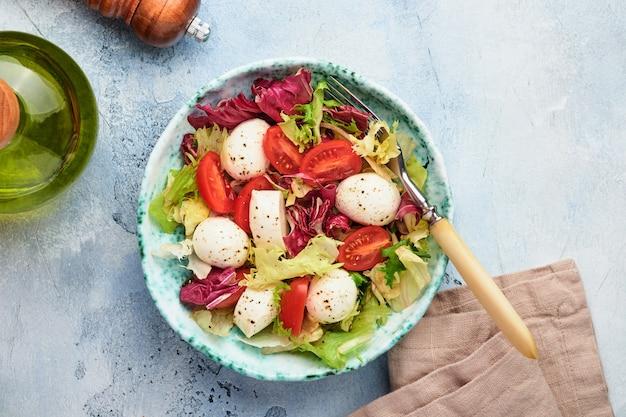 Mozzarella, tomaat en mix van verse slablaadjes, leisteen stenen tafel achtergrond, bovenaanzicht. bespotten.