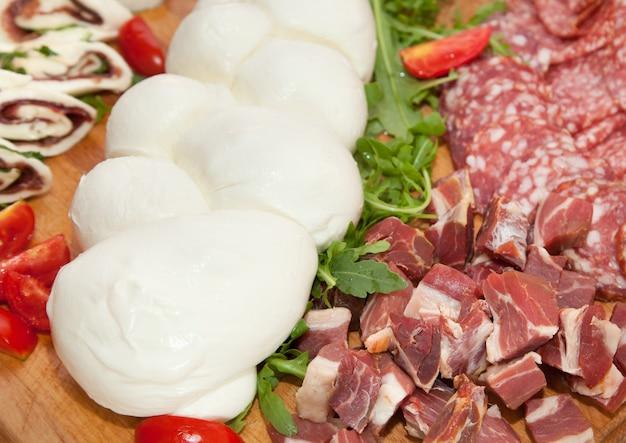 Mozzarella vormige vlecht op snijplank met salami en kaas.