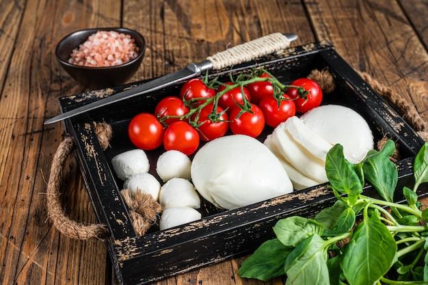 Mozzarellakaas, basilicum en tomatenkers in houten dienblad, caprese-salade. houten achtergrond. bovenaanzicht.