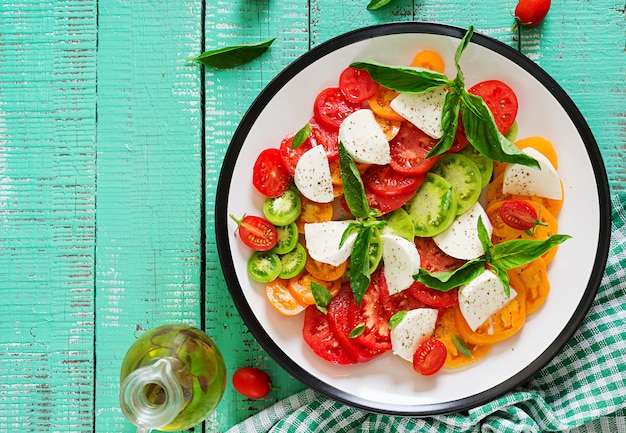Mozzarellakaas, tomaten en basilicumkruidbladeren in plaat op de witte houten lijst. caprese salade. italiaans eten. bovenaanzicht