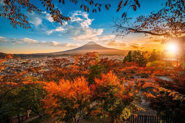 Mt. fuji met rood blad in de herfst op zonsondergang in fujiyoshida, japan.